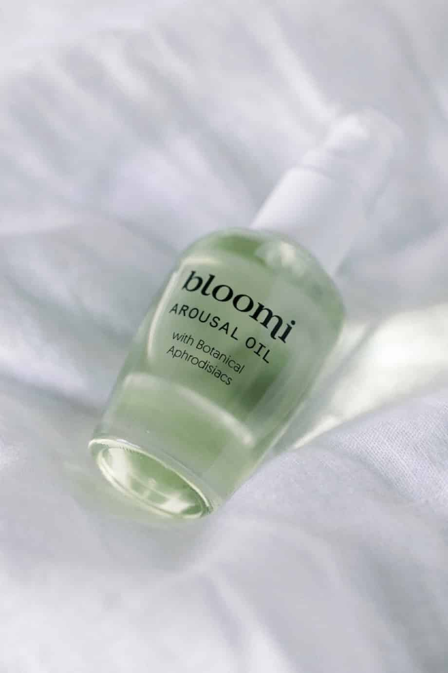 The Bloomi Arousal Oil lays on a bed showing off the packaging label design.