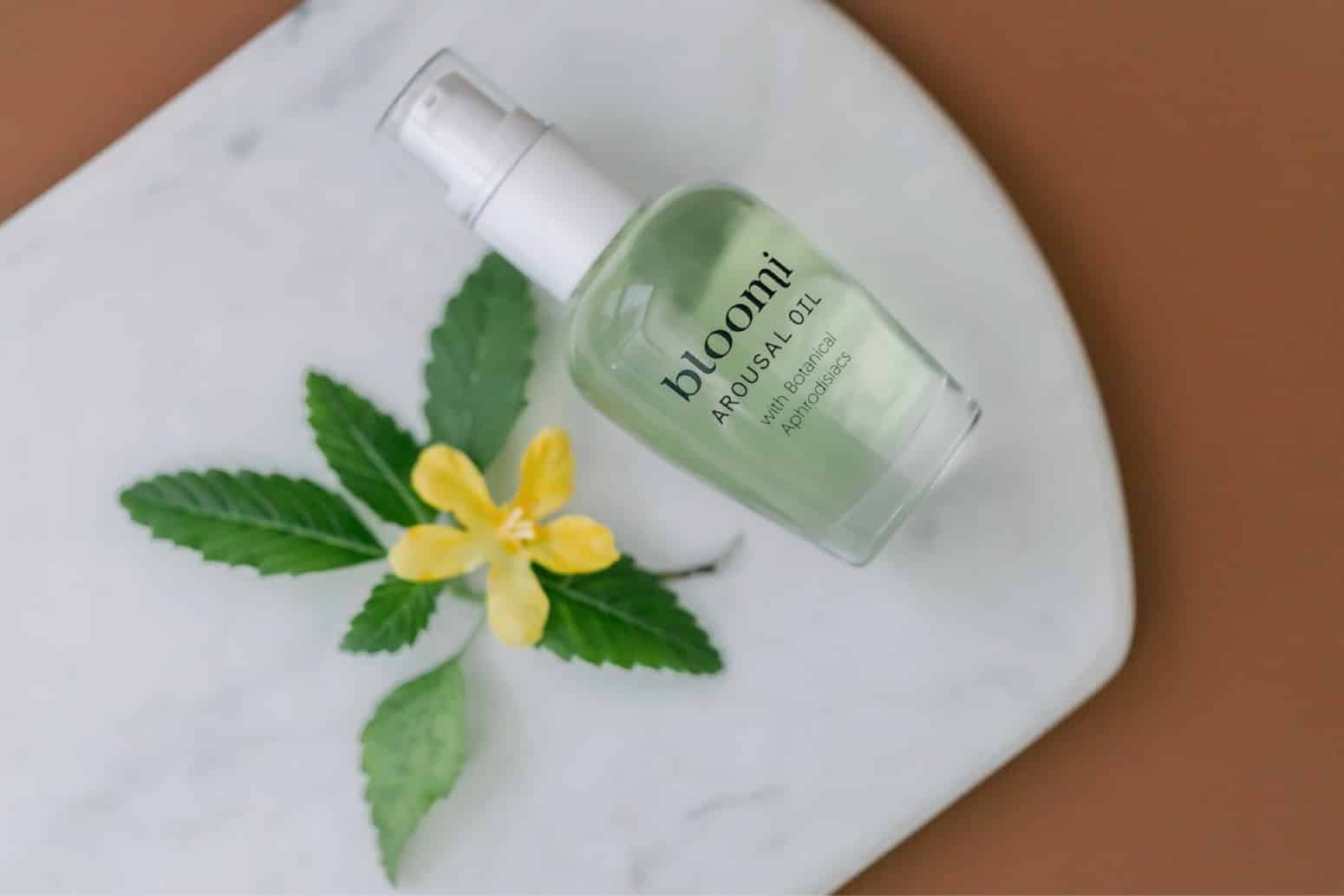 The Bloomi Arousal Oil product lays on a marble surface with a damiana flower–one of the key ingredients–nearby.