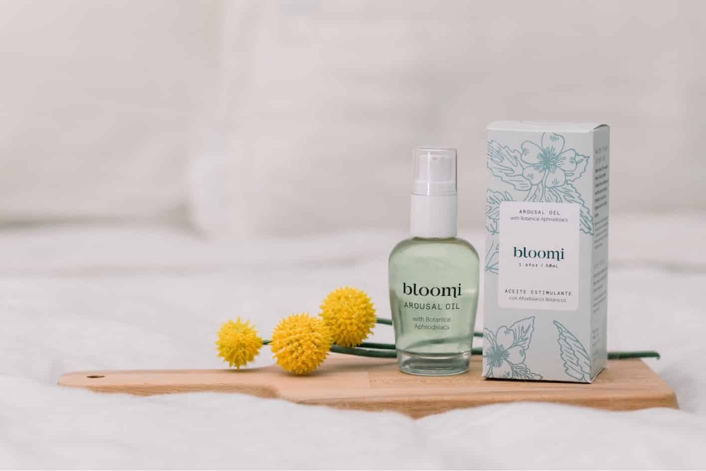 The Bloomi oil sits on a board, showing off the pack and label design